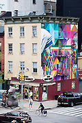 Street corner scene with cyclist, traffic lights, mural and Chelsea Square Market store at West 18th Street and Tenth Avenue in New York City, USA