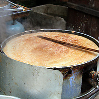 Asia, China, Chongqing. Local specialty, a Sichuan pancake, cooks to perfection in Chongqing street market.