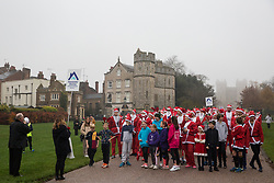 Windsor, UK. 24 November, 2019. Admiral Sir James Francis Perowne KBE (l), Constable and Governor of Windsor Castle, announces the start of the 2019 Windsor Santa Dash for fun runners dressed as Santa Claus and his reindeer on the Long Walk in front of Windsor Castle in aid of the Alexander Devine children's hospice.