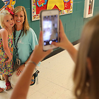 Paisley Jane Russell, a Kindergartner at Saltillo Primary School, stands with her mother, Tabitha, as her older sister Kalianna takes their picture on the first day back to school for students in Lee County Thursday morning in Saltillo.