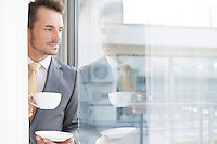 Thoughtful businessman having coffee in office