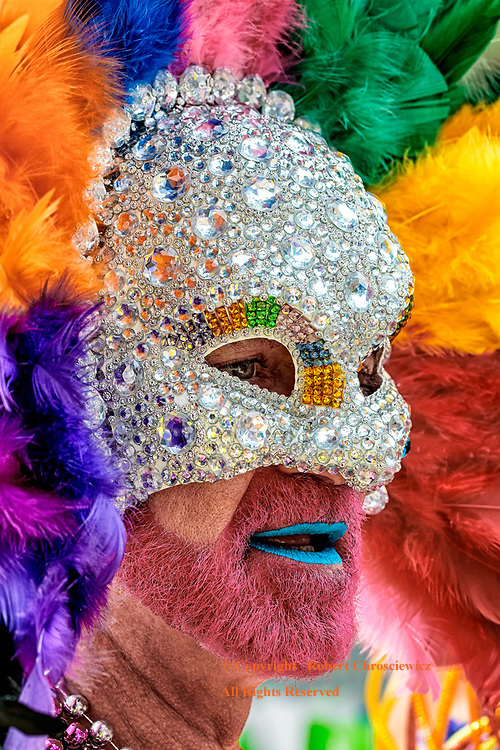 Peacock Pride: This man readies himself, behind this elaborate sequined face-mask and feathered headdress, for his place in the Gay Pride Parade, Vancouver British Columbia Canada.