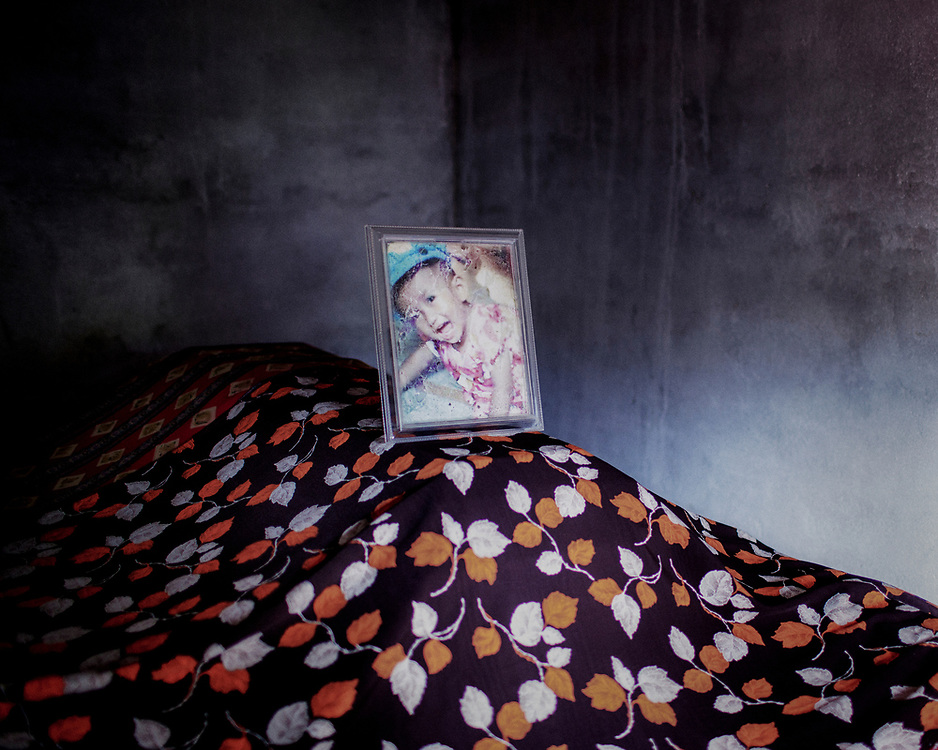 A coffin with a portrait of a deceased family member is seen inside a tomb.<br />
