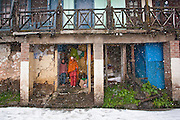 A mother and her daughter taking shelter in an old house at Jakhu, Shimla during the seasons first snowfall at Shimla, Himachal Pradesh