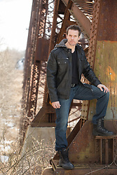 Good looking man by a railroad trestle