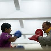 Le coach du Bhiwani Boxing Club Ms. Singh reste sur le ring à la fin de la journée pour entraîner une  jeune fille qui d'ici deux semaines se battra dans une competition