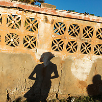 Madagascar, Tulear, Shadows cast on concrete wall by young woman walking toward beach at sunset
