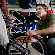 July 23, 2010 - Bronx, NY : Ian Jacob, owner of the newly opened United Spokes bike shop on West 242nd Street and Broadway, attends to a customer's tires.