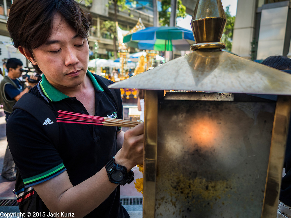 19 AUGUST 2015 - BANGKOK, THAILAND:  A man lights incense before praying at Erawan Shrine during the reopening of the shrine. Erawan Shrine in Bangkok reopened Wednesday morning after more than 20 people were killed and more than 100 injured in a bombing at the shrine Monday, August 17, 2015. The shrine is a popular tourist attraction in the center of Bangkok's high end shopping district and is an important religious site for Thais. No one has claimed responsibility for the bombing.     PHOTO BY JACK KURTZ