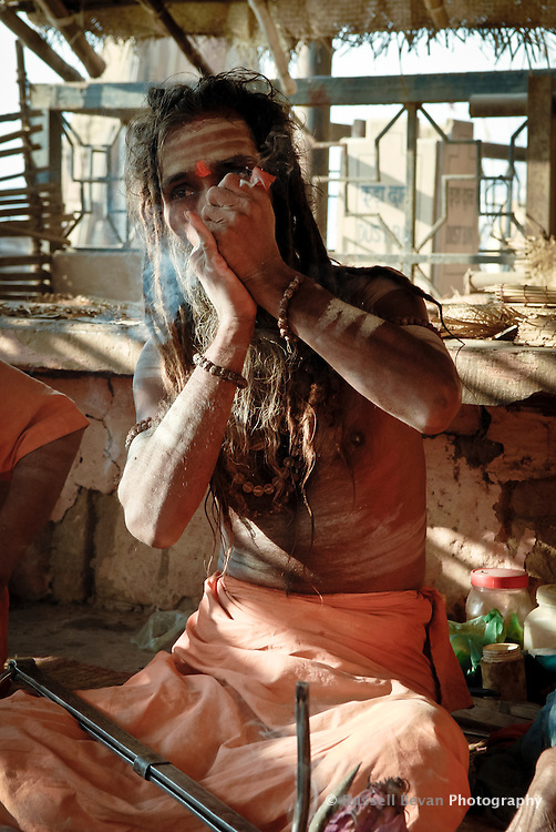 A Hindu holy man smoking a chillum at the ghats in Varanasi, Uttar Pradesh, India