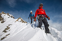 A male mountaineer leads on a traverse of a snowy ridge of Aiguilles Marbrées.