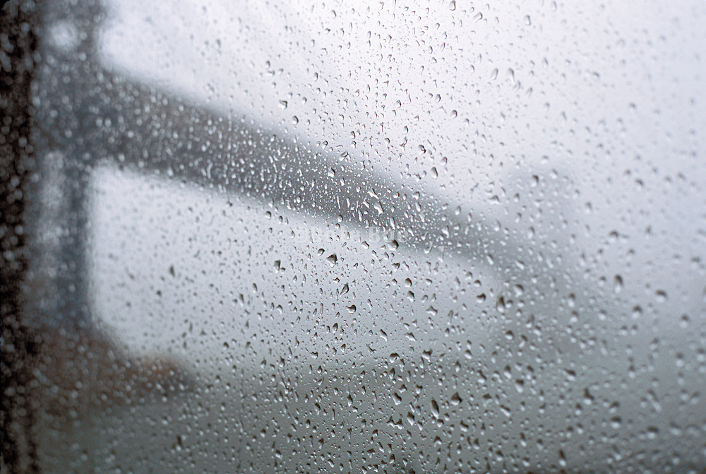 Rain drops on a window with a view of a bridge