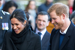 © Licensed to London News Pictures. 18/01/2018. Cardiff, UK. Prince Harry and Meghan Markle arrive at Cardiff Castle to visit the Wales Culture Fair. Secretary of State for Wales Alun Cairns is pictured between them. Photo credit : Tom Nicholson/LNP