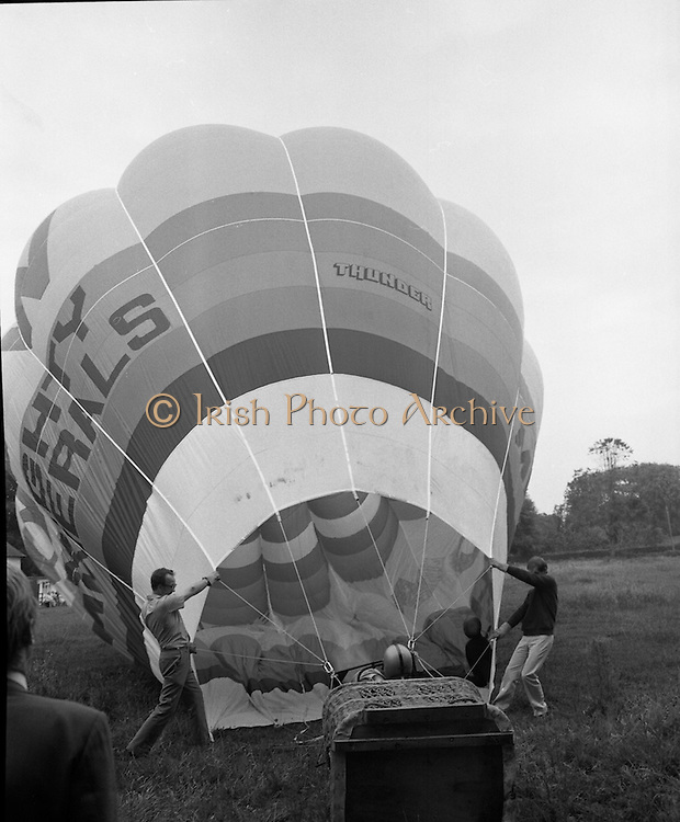 Dew Mighty Minerals Hot Air Balloon.   (H15)..1974..07.08.1974..08.07.1974..7th August 1974..The launching of the Dew Mighty Minerals hot air balloon,took place in Tullamore,Co Offaly last night,as part of the Tullamore Festival Week. The balloon was piloted by Mr Wilf Woollett,a veterinary surgeon from Loughrea,Co Galway and his co-pilot was Kevin Haugh. Miss Rosemary Mannion,the Offaly Rose of Tralee contestant sent the balloon on its way by popping a bottle of Champagne over it.  The balloon itself has a capacity of 56,000 cubic feet,is 60ft high and 50ft wide. It is made from nylon/polyproplene. The basket is 2ft square by 3ft high and carries two people,it is attached to the balloon by steel cables..Wilf Woollett has piloted the balloon in the U.S. and Britain and is a member of the Dublin Balloon Club...Picture shows the balloon being inflated under the watchful eyes of Wilf Woollett,right,and co-pilot Kevin Haugh standing inside.