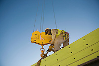 Workman fixes harness of hook block to building material
