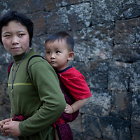 Jiang Yinghui, 15 years-old at right, carries young Ying Shenjiang, 2 years-old, on her back in a traditional child carrier seen all across southwestern China, in Heshun old town. The stone blocks behind them are the foundations made of lava stone mined from the neighboring extinct volcanoes.