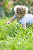 Young child crawling across grass with a flower bush in the background