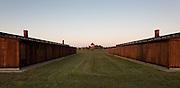 Wooden barracks in Auschwitz II - Birkenau with perimeter fence and guard tower. Auschwitz II-Birkenau Extermination Camp (Poland)
