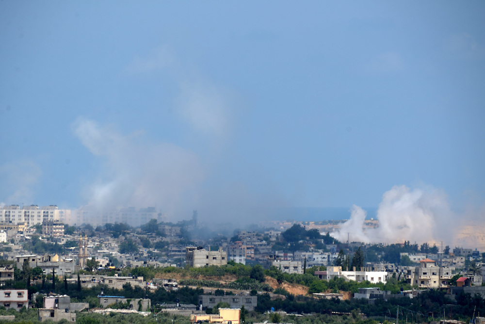 ISRAEL-GAZA BBORDER, ISRAEL - JULY 18, 2014: Smoke rises from buildings after being hit by Israeli Army artilery, in Northern Gaza  Strip, as seen from the Israeli border, on July 18, 2014. Israel has launched a ground invasion into Gaza Strip, targeting terror tunnels. Photo by Gili Yaari.
