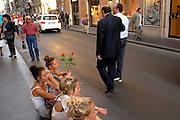 Rome, Italy 101411 Young women taek a break and sit on the curb at Via del Corso, one of Rome's best well-known shopping areas. (Essdras M Suarez/ EMS Photography)