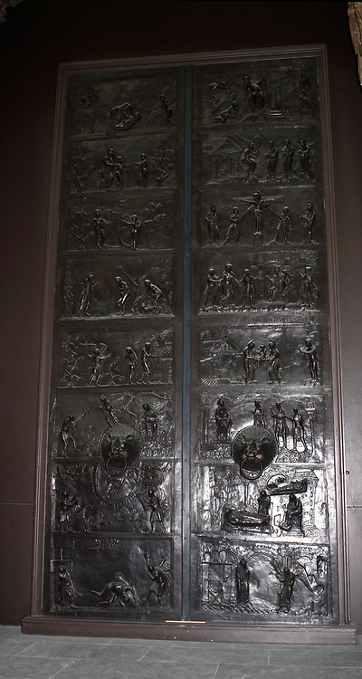 Bronze doors with scenes from the Old and New Testament in relief. Made at the order of St. Bernward, and set up by him in 1015 at St. Michael's Church, Hildesheim. The left side shows the Creation of Eve, the Presentation of Eve to Adam, the Temptation, the Fall, The Expulsion, the Labours of Adam and Eve, the Sacrifice of Abel and Cain, the Murder of Abel. The right side shows the Annunciation, the Nativity, the Adoration of the Magi, the Presentation to Simeon, Christ before Pilate, the Crucifixion, the Maries at the Sepulchre, and Christ appearing to St. Mary Magdelen.
