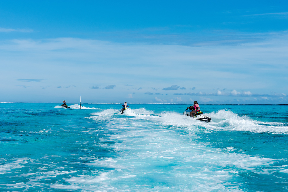 Moorea Island, French Polynesia--March 17, 2018. Jet ski riders skim over the waters of a blue lagoon off the coast of Moorea Island. Editorial use only.