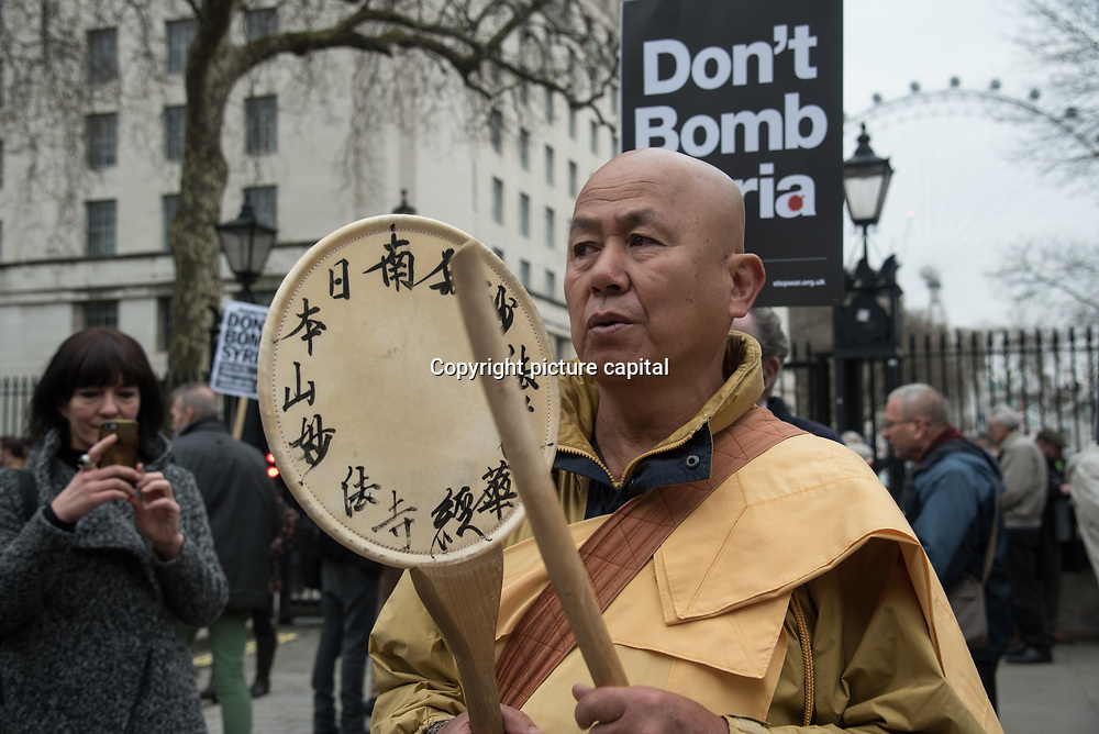 Hundreds of protestors holding placards join Stop the War Coalition hosts a Protest against Trump & May - No More Bombs on Syria on 13 April 2018 outside Downing Street, London, UK.