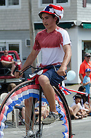 BAR HARBOR, MAINE, July 4, 2014. A young man rides an old-fashioned bicycle in the Independence Day Parade