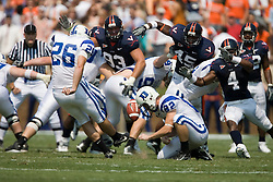 Virginia defensive end Alex Field (93), Denzel Burrell (45), and Vic Hall (4) disrupt a Duke kicker Joe Surgan (26) field goal attempt in the first half.  The Virginia Cavaliers defeated the Duke Blue Devils 23-14 at Scott Stadium in Charlottesville, VA on September 8, 2007  With the loss, Duke extended their longest-in-the-nation losing streak to 22 games.