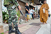 "Sept. 25, 2009 -- PATTANI, THAILAND: Soldiers and police officers accompany Buddhist monks on their morning rounds soliciting alms in Pattani, Thailand. Monks have been the targets of Muslim insurgent assassins who kill representatives of Thai Buddhist culture include monks and teachers. Thailand's three southern most provinces; Yala, Pattani and Narathiwat are often called ""restive"" and a decades long Muslim insurgency has gained traction recently. Nearly 4,000 people have been killed since 2004. The three southern provinces are under emergency control and there are more than 60,000 Thai military, police and paramilitary militia forces trying to keep the peace battling insurgents who favor car bombs and assassination.  Photo by Jack Kurtz / ZUMA Press"