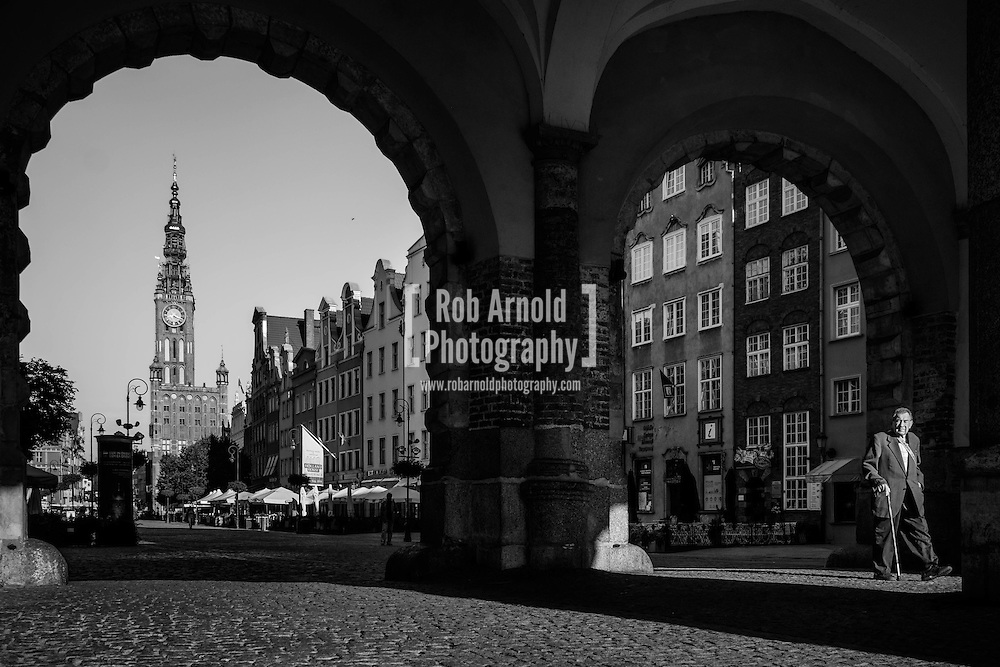 An elderly man walking through the arches of the Green Gate in the Old Town in Gdansk, Poland