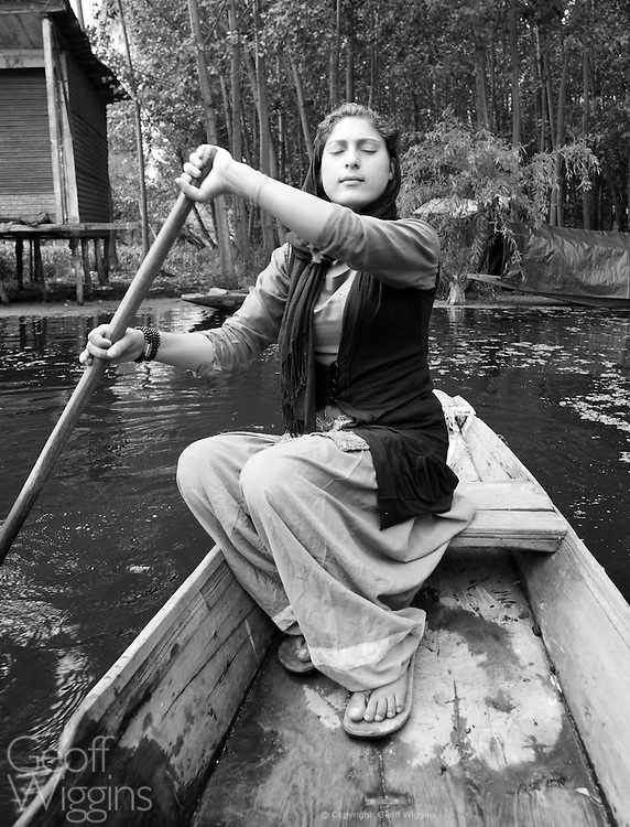 Indian girl from small fishing community rows sinking boat on Dal Lake, Srinagar, Jammu and Kashmir State, India