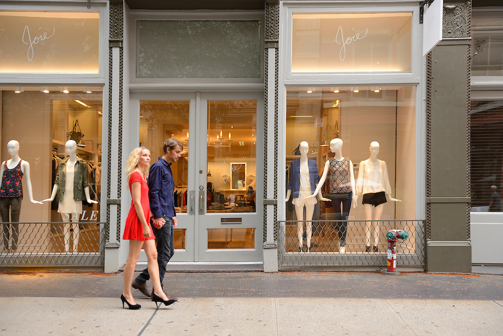 Couple passing shop in Soho,New York, Manhattan, USA<br /> Model release 0341,0340