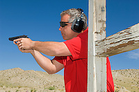 Man aiming hand gun at firing range