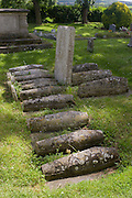Visitors inspect the row of childrens' graves in the churchyard of St James, Cooling, Kent. Charles Dickens wrote about these graves in the opening of his famous novel Great Expectations. Dickens lived nearby in Higham and referred to this row of children's tombstones now inevitably referred to as Pip's graves. Dickens pictures them as '....five little stone lozenges each about a foot and a half long which were arranged in a neat row ... and were sacred to the memory of five little brothers of mine....' In fact the Cooling graves belong to the children of two families, aged between 1 month and about a year and a half, who died in the late 18th and 19th centuries.