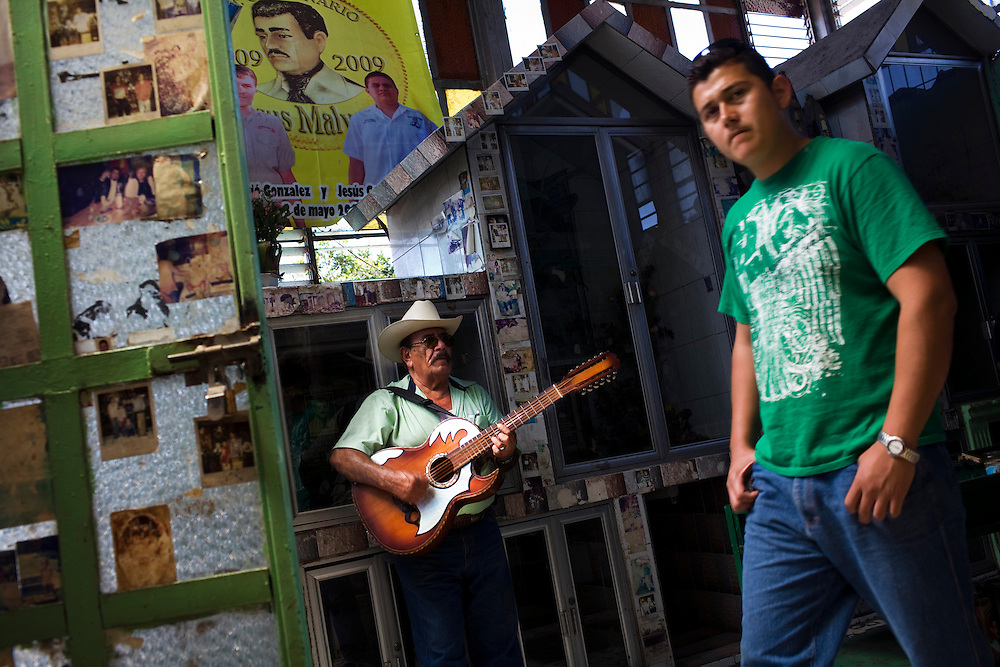 A man plays guitar in a chapel devoted to Jesus Malberde, as a youth in a shirt ofen associated with narco culture walks by, in Culiacan, Mexico.  Malverde is a folk saint worshipped by many people in the underworld and often associated with narcoculture and drug dealers. He is thought of as the Mexican version of Robin Hood, looking after those who have been forgotten by the Church and are involved in a life of crime.  People come to the chapel to show their respect and pray.