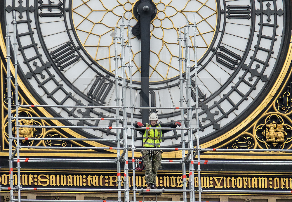 © Licensed to London News Pictures. 10/10/2017. A worker pauses to look at the view as he helps erect 96 meters of scaffolding up to the clock face of The Elizabeth Tower - home of the Big Ben bell at The Houses of Parliament.  The work is part of a three-year programme to conserve the Great Clock, the tower and Big Ben. London, UK. Photo credit: Peter Macdiarmid/LNP