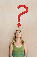 Woman leaning against wall with painted question mark