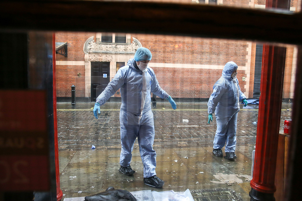 © Licensed to London News Pictures. 03/03/2019. London, UK. Forensic officer near the clothing with blood stains at the rear entrance of The Coach and Horses pub in Romilly Street in Soho. According to the police, a man aged 30 yrs old is seriously injured in hospital and a woman has been arrested. Photo credit: Dinendra Haria/LNP