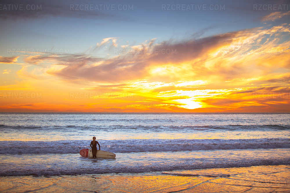 A woman holding her surfboard and walking into the ocean at sunset in San Clemente, California. Photo by Robert Zaleski/rzcreative.com