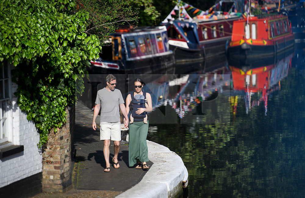 © Licensed to London News Pictures. 07/05/2018. London, UK. A couple walking in early morning sunshine at day three of the Canalway Cavalcade festival takes place in Little Venice, West London on Monday, May 7th 2018. Today is expected to be the hottest May bank holiday Monday on record. Photo credit: Ben Cawthra/LNP