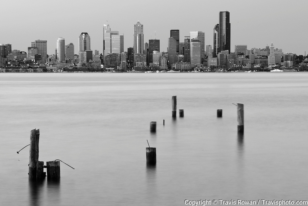 A dramatic night time view of the Seattle skyline and old dock pilings in Puget Sound.