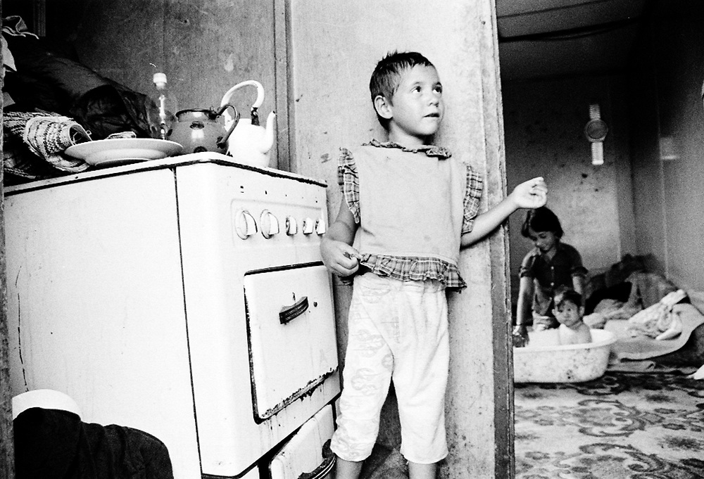 The Dzevdet family in their container...Romas children do not receive the same attention as the other IDPs children: they do not go to school and they do not receive any assistance as far as health is concerned. Because the families did not have documents, they could not be registered officially as IDPs...During the summer1999, over 245,000 Serbs and Roms fled to Serbia and Montenegro from or within Kosovo in fear of reprisals from the majority Albanian population, after NATO air strikes had forced the withdrawal of Yugoslav. In 2003, less than 2% of them had returned and a large number of these internally displaced persons (IDPs) were still living in camps in very difficult conditions..In addition, around 5,000 IDPs, mainly of Roma ethnicity, are living in unrecognized collective centres, makeshift huts, corrugated metal containers and other substandard shelters. .This work was meant to look at how the life of children and young adults is affected by the fact that they are IDPs. I asked myself more specifically what would be different for these children/young adults from the 'normal' people of their age as far as education, health, social life, family, 'love' life and leisure are concerned. ..La famille Dzevdet dans leur container...Les enfants roms ne vont pas à l'école et ne reçoivent aucune assistance médicale. Faute de papiers d'identité, ils n'ont pu être officiellement enregistrés en tant qu'IDP...Pendant l'été 1999, plus de 245 000 serbes et roms ont fuit le Kosovo pour chercher refuge en Serbie ou au Montenegro, par peur de représailles de la part de la majorité de la population albanaise après que les forces de l'OTAN aient forcé l'armée yougoslave à se retirer. En 2003, moins de 2% d'entre eux étaient rentrés chez eux et le plus grand nombre de ces 'déplacés' (IDPs) vivaient encore dans des centres d'accueil dans des conditions très difficiles..Environ 5 000 IDPs, la plupart romas, vivent dans des centres non reconnus faits de containers ou d'abris de for