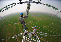Electrician examines and repairs the rural power grid