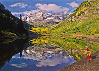 A young child throws a stone into the reflection of Maroon Bells in Maroon Lake.  Elk Mountains, Colorado.