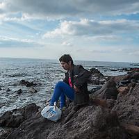 GRIECHENLAND, Lesbos, Mithymna/Molivos, 28.10.2015 / Refugee am Strandufer: In der Nacht zuvor kam es zu einem schweren Bootsunglueck vor der Kueste. Rettungskraefte konnten mindestens 242 Menschen retten, waehrend elf Menschen nur noch tot gebogen werden konnten. Die Kuestenwache geht davon aus, dass die Zahl der Toten noch deutlich steigen wird. Nachdenklich sitzt dieser Mann eine halbe Stunde allein auf diesem Felsen und kaut auf Sonnenblumenkernen.