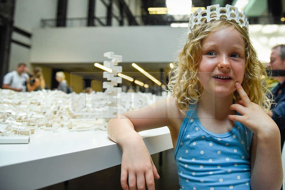 "© Licensed to London News Pictures. 26/07/2019. LONDON, UK. Willow Beal, aged 5, poses with a Lego crown at the preview of ""The cubic structural evolution project"", 2004, by Olafur Eliasson at Tate Modern.  Exhibited for the first time in the UK, the artwork comprises one tonne of white Lego bricks inspiring visitors to create their own architectural vision for a future city and is on display until 18 August 2019.  The work coincides with the artist's new retrospective exhibition ""In real life"" at Tate Modern on display to 5 January 2020. (Parental permission to photograph obtained). Photo credit: Stephen Chung/LNP"