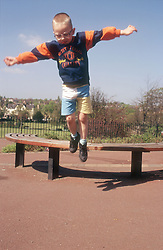 Young boy jumping off bench in park,