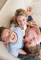 Raised view of laughing brother and sister piled on mother's lap with son smiling up to camera