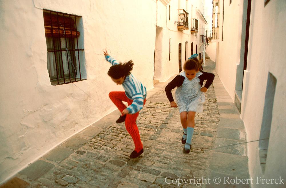 SPAIN, ANDALUSIA VEJER DE LA FRONTERA; near Cadiz, a traditional Moorish style village or 'pueblo blanco'; girls jumping rope
